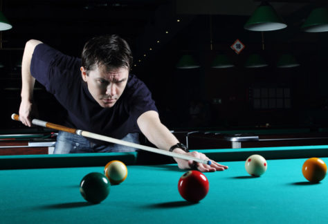 Man learning to play snooker in the dark club.